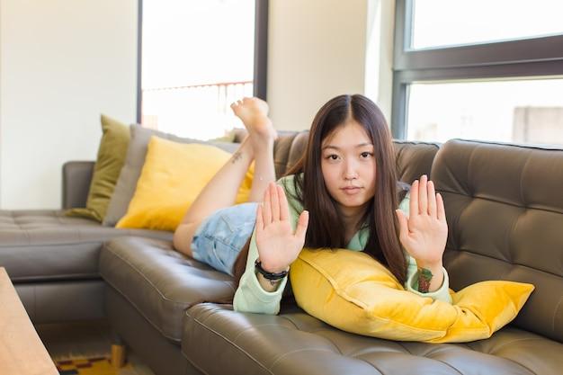 真面目で、不幸で、怒って、不機嫌そうに見える若いアジア人女性は、立ち入りを禁じているか、両方の手のひらを開いて停止すると言っています