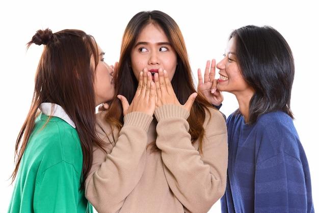 Молодая азиатская женщина выглядела шокированной, а оба друга шептались с каждой стороны