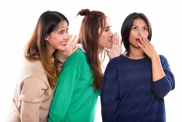 Молодая азиатская женщина выглядит потрясенной, когда оба друга шепчутся на одной стороне