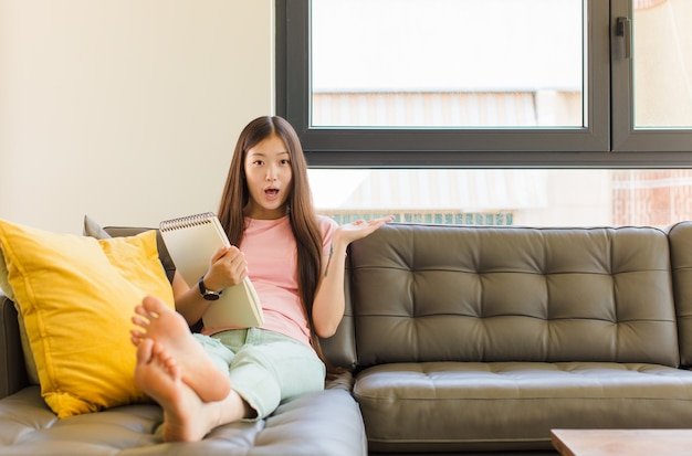 턱이 측면에 열린 손으로 물건을 들고 떨어졌다 놀란 충격을 찾고 젊은 아시아 여자