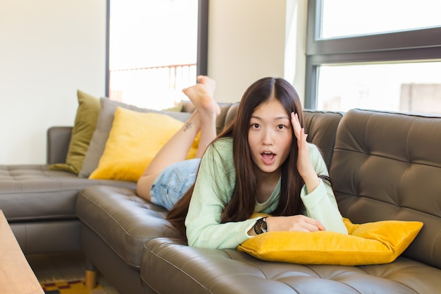 Young asian woman looking surprised, open-mouthed, shocked, realizing a new thought, idea or concept