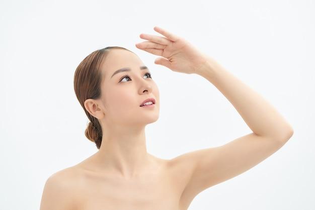 光を覆うために見上げて手を見せている若いアジアの女性。