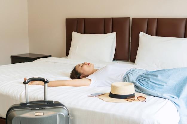 ホテルの部屋のベッドに横たわっている若いアジアの女性。旅行のコンセプト
