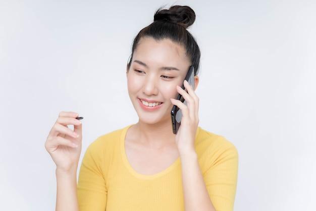 Молодая азиатская женщина, лежащая на мобильном телефоне
