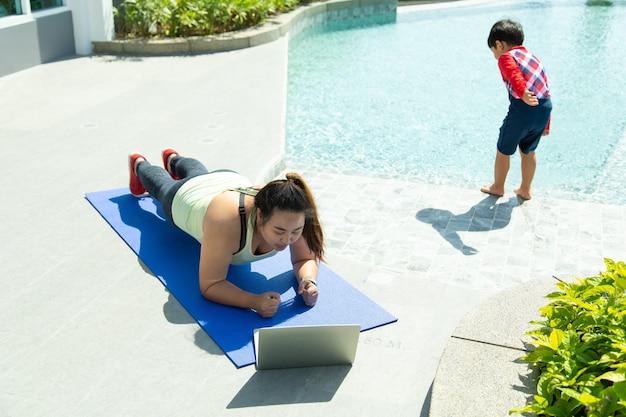 Молодая азиатская женщина, лежащая на коврике для йоги, для онлайн-обучения, пока ребенок играет. концепции здорового образа жизни и спорта.