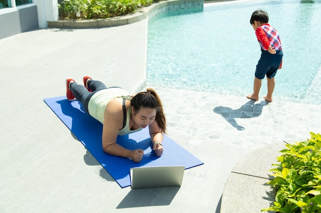 Young asian woman lying on yoga mat for online training while the kid is playing around. healthy lifestyle and sport concepts.