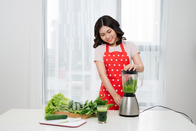 Young asian woman making green detox smoothie in kitchen at home.