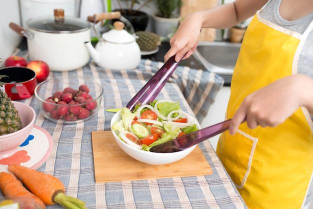 家で幸せに笑って笑ってキッチンでサラダを作る若いアジアの女性。