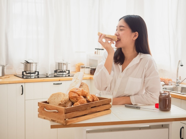 Young asian woman making sandwiches and eat bread in kitchen