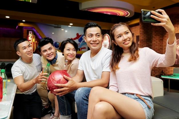 ボウリングをしながら友達と一緒に携帯電話で自分撮りをするアジアの若い女性
