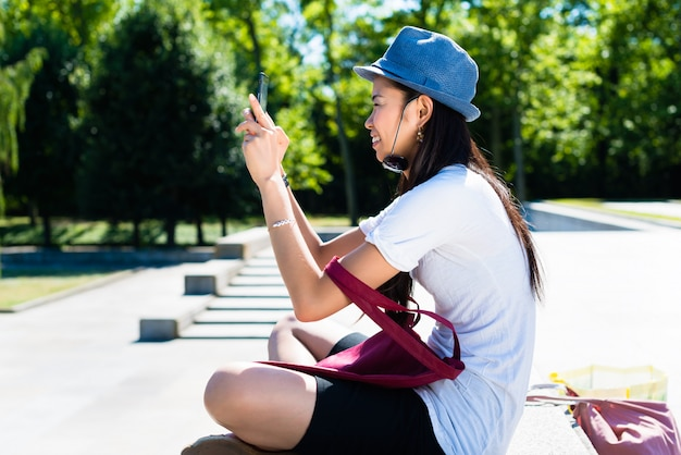 Young asian woman making selfie pictures