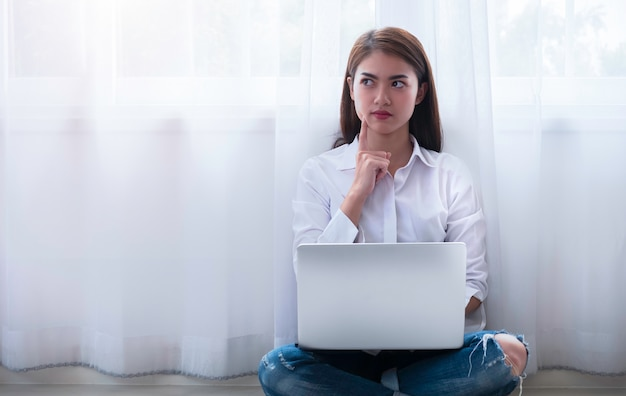 Young asian woman making serious decision while sitting on floor and using laptop.