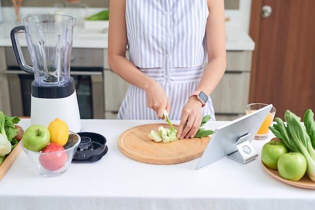 Молодая азиатская женщина делает смузи по рецепту в планшете