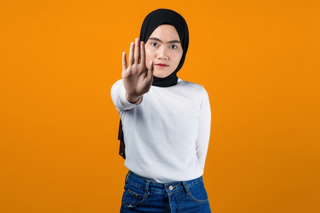 Young asian woman making stop gesture with her hands