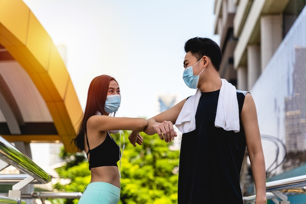 Young asian woman and man wearing protective face masks greeting bumping elbows in city, people in facial covers protect from covid-19 coronavirus in office, healthcare concept