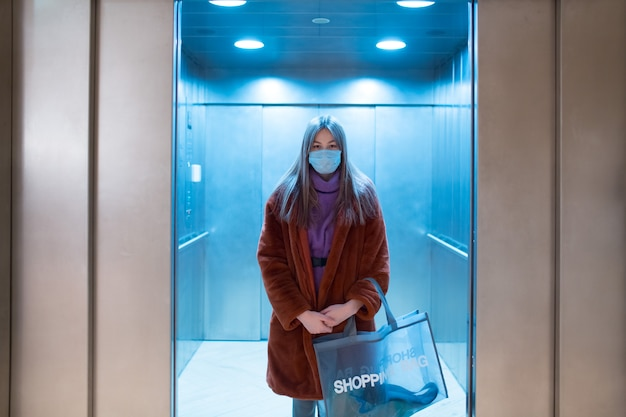 Young asian woman in medical mask in elevator indoors