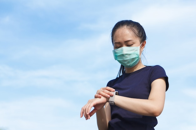 Young asian woman in medical protective mask doing setting smart watch application before exercise in the morning.working out outdoor. concept of healthy