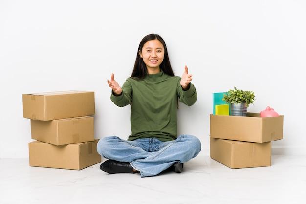 若いアジアの女性が新しい家に移動すると自信を持って抱擁を与える