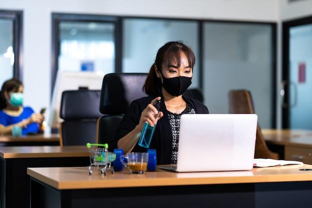 コロナウイルスcovid-19に対してデスクオフィスのラップトップコンピューターを掃除するワイプに若いアジアの女性役員消毒スプレー