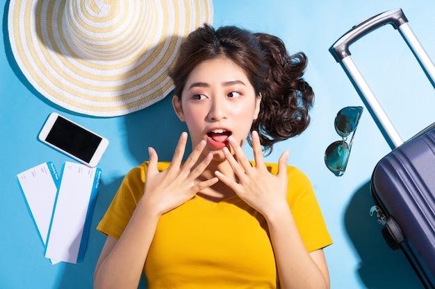 Молодая азиатская женщина на синем, летнем и путешествующем концепте