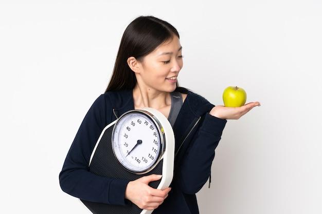 Молодая азиатская женщина на белой стене держа веся машину пока смотрящ яблоко