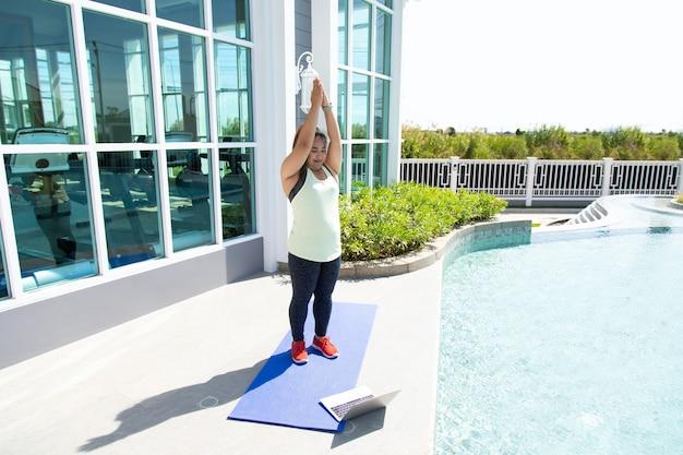 Молодая азиатская женщина на коврике для йоги делает онлайн-обучение. концепции здорового образа жизни и спорта.