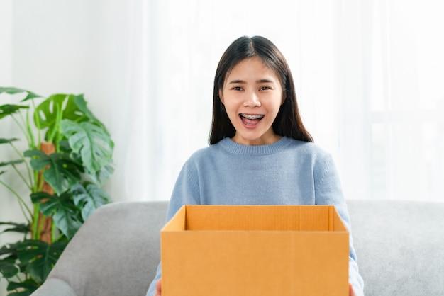 Молодая азиатская женщина раскрывая коробку пока сидящ на софе