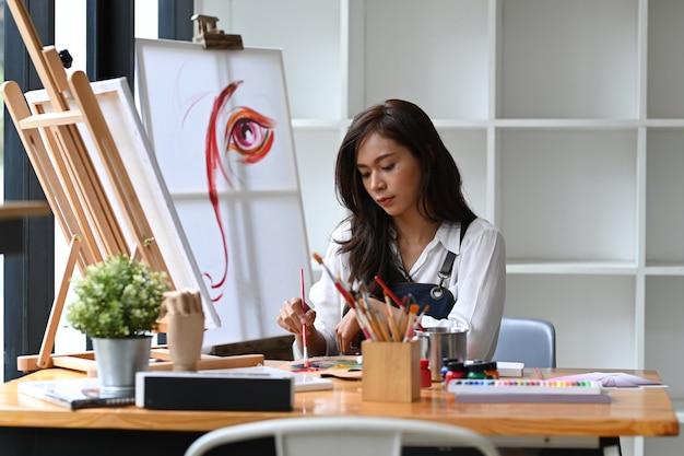 水彩で絵を描く若いアジアの女性。