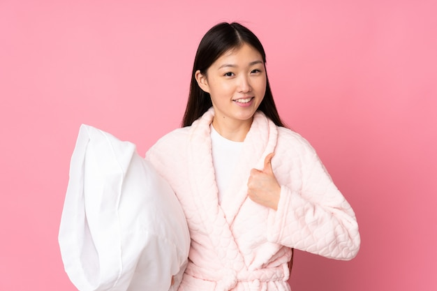 Young asian woman in pajamas on pink wall with thumbs up because something good has happened