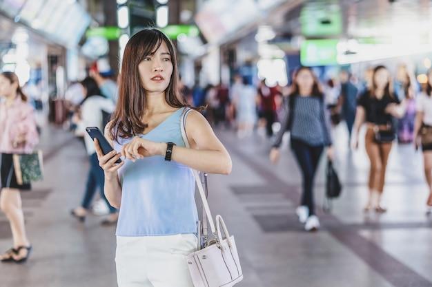 젊은 아시아 여성 승객이 시간을 확인하고 지하철에서 친구를 기다리고 있다