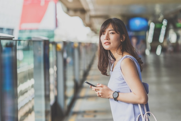 Молодая азиатская женщина-пассажир проверяет время и ждет своего друга в метро