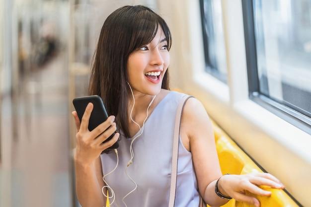 地下鉄の電車の中でスマートな携帯電話を介して音楽を聴く若いアジアの女性の乗客