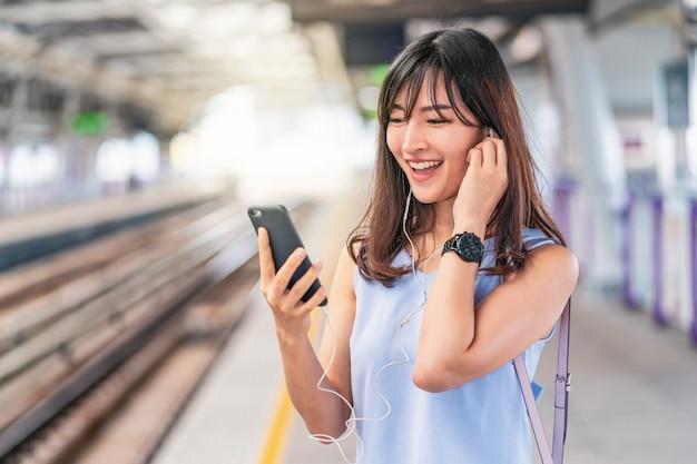 Молодая азиатская женщина-пассажир, слушающая музыку через умный мобильный телефон