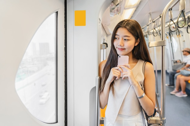 Young asian woman passenger using social network via smart mobile phone in subway trai