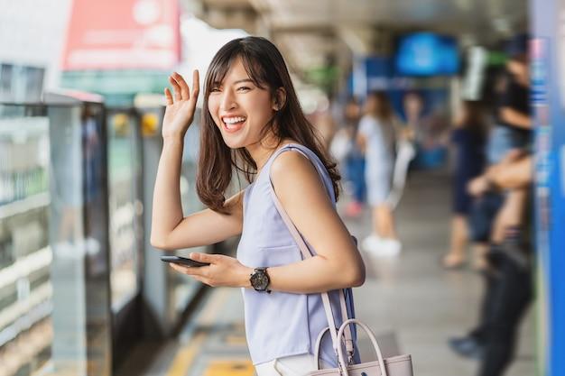Пассажир молодой азиатской женщины машет рукой для приветствия своему другу в поезде метро