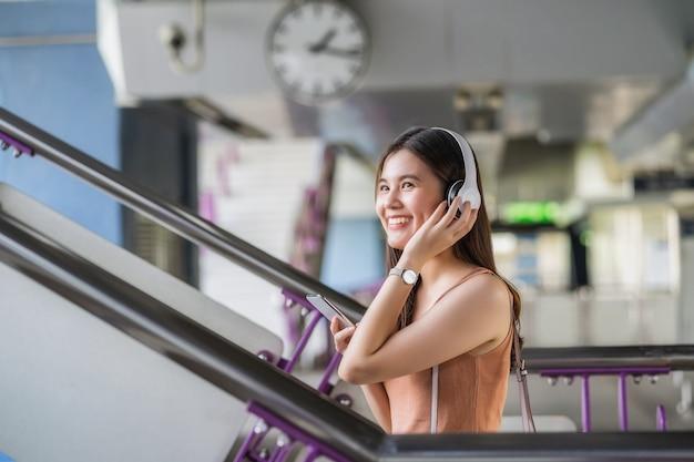 헤드폰을 끼고 스마트 휴대폰을 사용하여 음악을 듣는 젊은 아시아 여성 승객