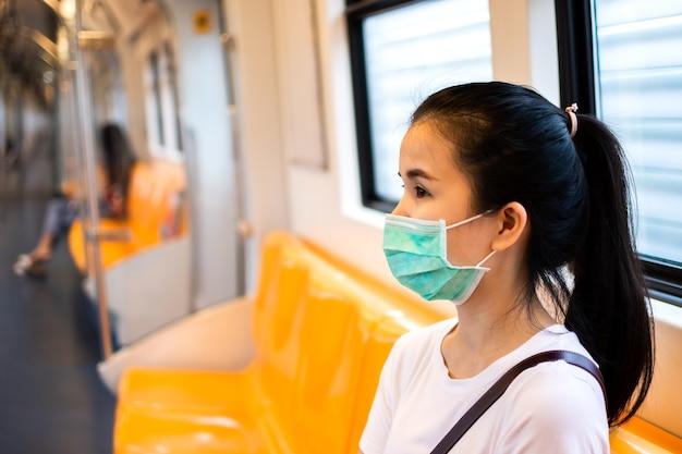 지하철이나 스카이 트레인 안에 앉아 의료용 안면 마스크를 쓴 젊은 아시아 여성 승객