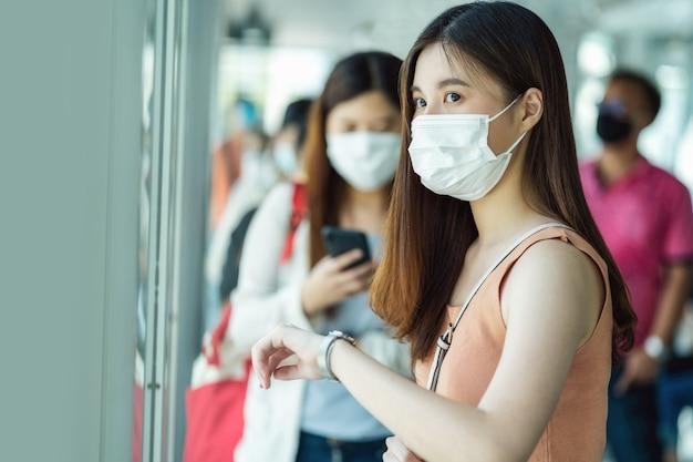 수술용 마스크를 쓰고 시간을 확인하는 젊은 아시아 여성 승객