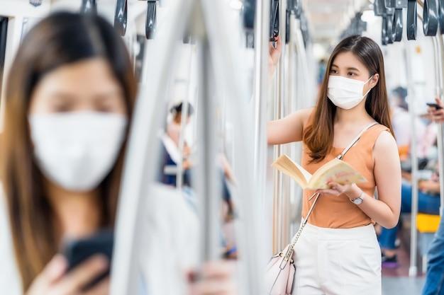 수술용 마스크를 쓰고 지하철에서 책을 읽는 젊은 아시아 여성 승객