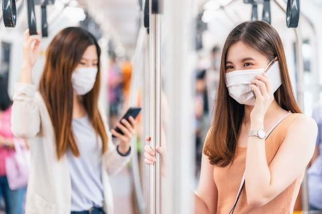 젊은 아시아 여성 승객이 수술용 마스크를 쓰고 스마트 휴대전화를 통해 함께 이야기합니다.