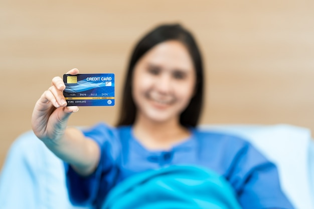 건강 신용 카드를 모의 들고 젊은 아시아 여자 환자. 건강 보험 개념