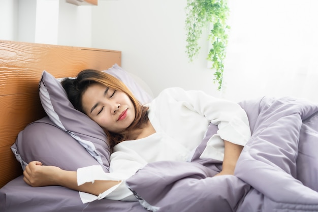 Young asian woman peacefully  sleeping well on comfortable soft bed