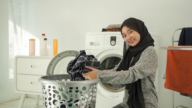 若いアジアの女性は家で洗うために汚れた服を拾います