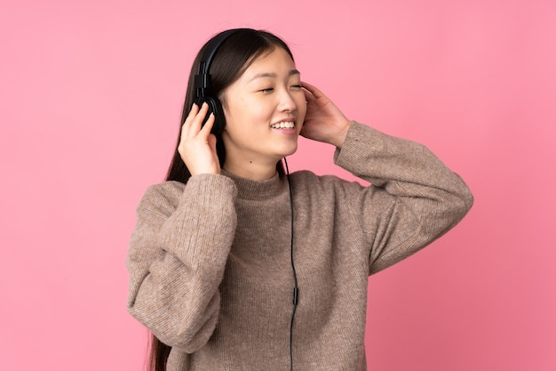 Young asian woman on pink wall listening music and singing