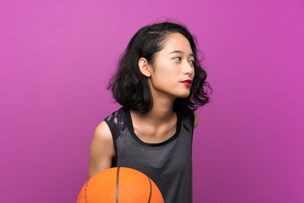 Young asian woman playing basketball over isolated purple background