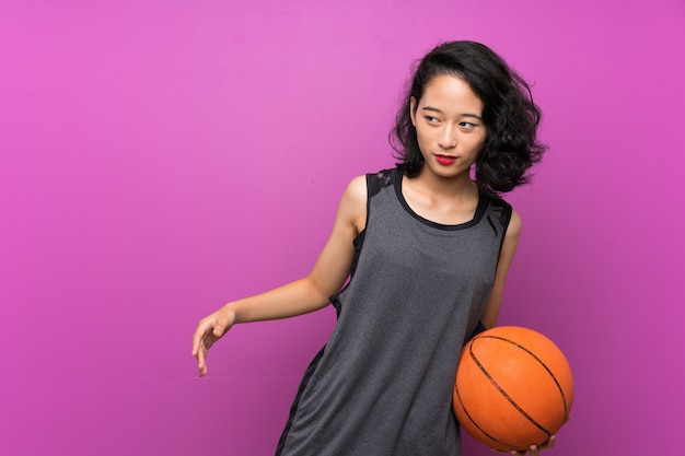 Young asian woman playing basketball over isolated purple wall