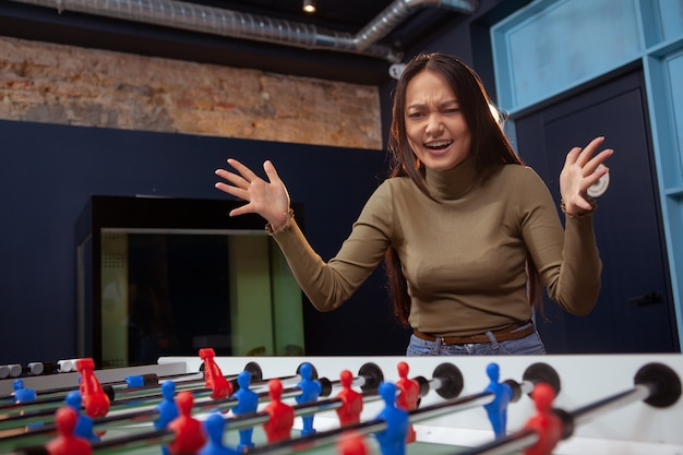 Young asian woman playing foosball