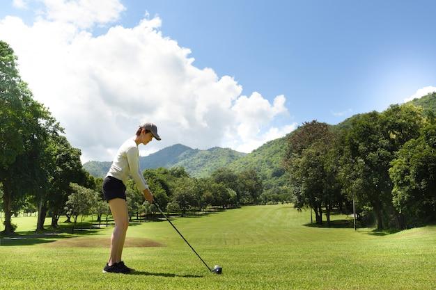 Молодая азиатская женщина играя гольф на красивом естественном поле для гольфа