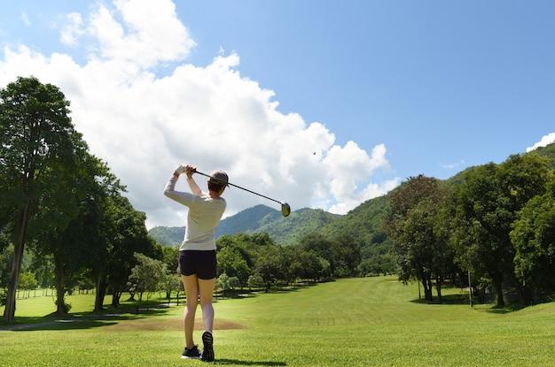 美しい自然のゴルフコースでゴルフをする若いアジア女性