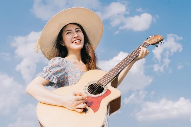 하늘 배경에서 기타를 연주하는 젊은 아시아 여성